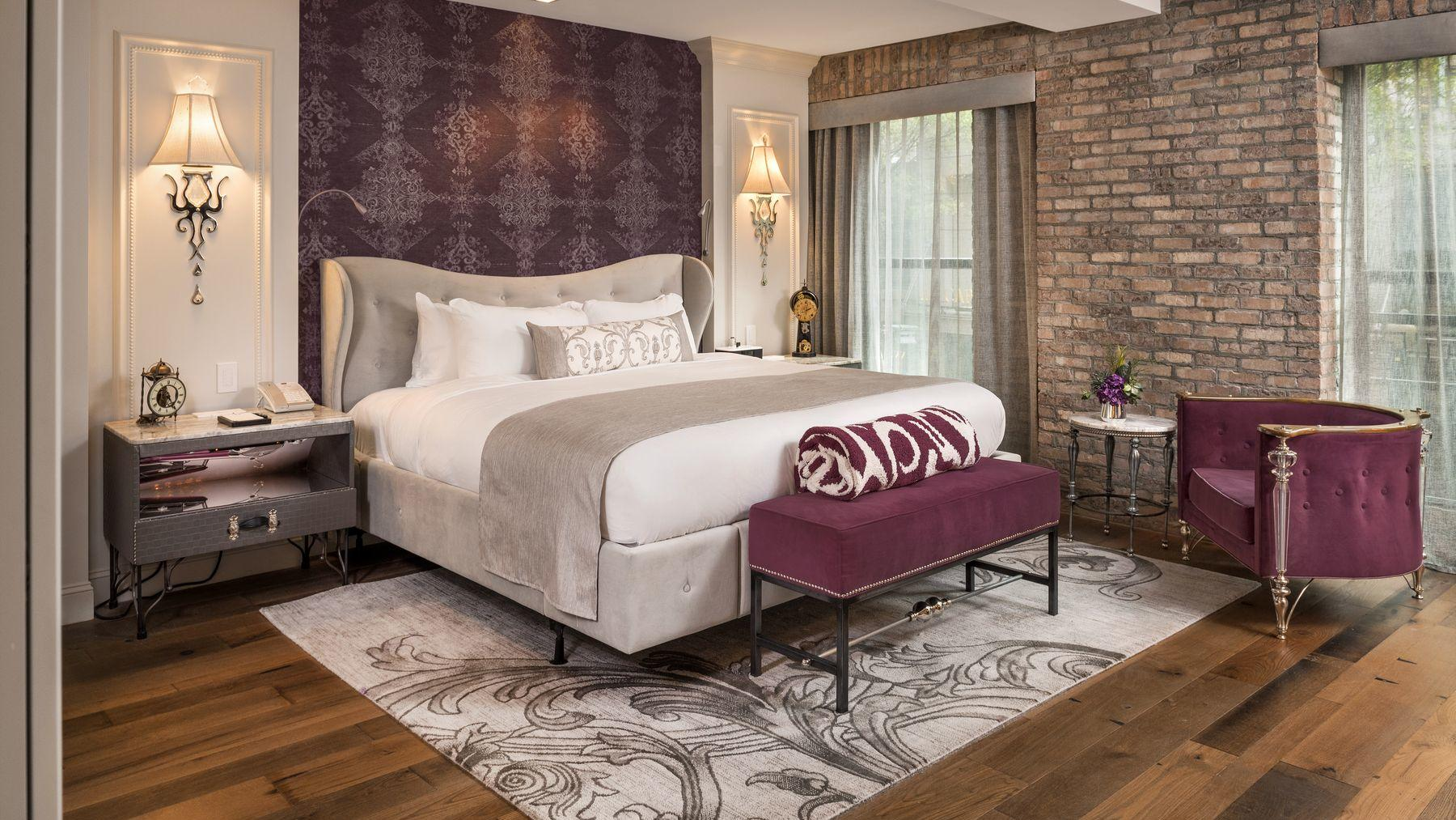 bed in cozy brick room with carpet and floral headboard