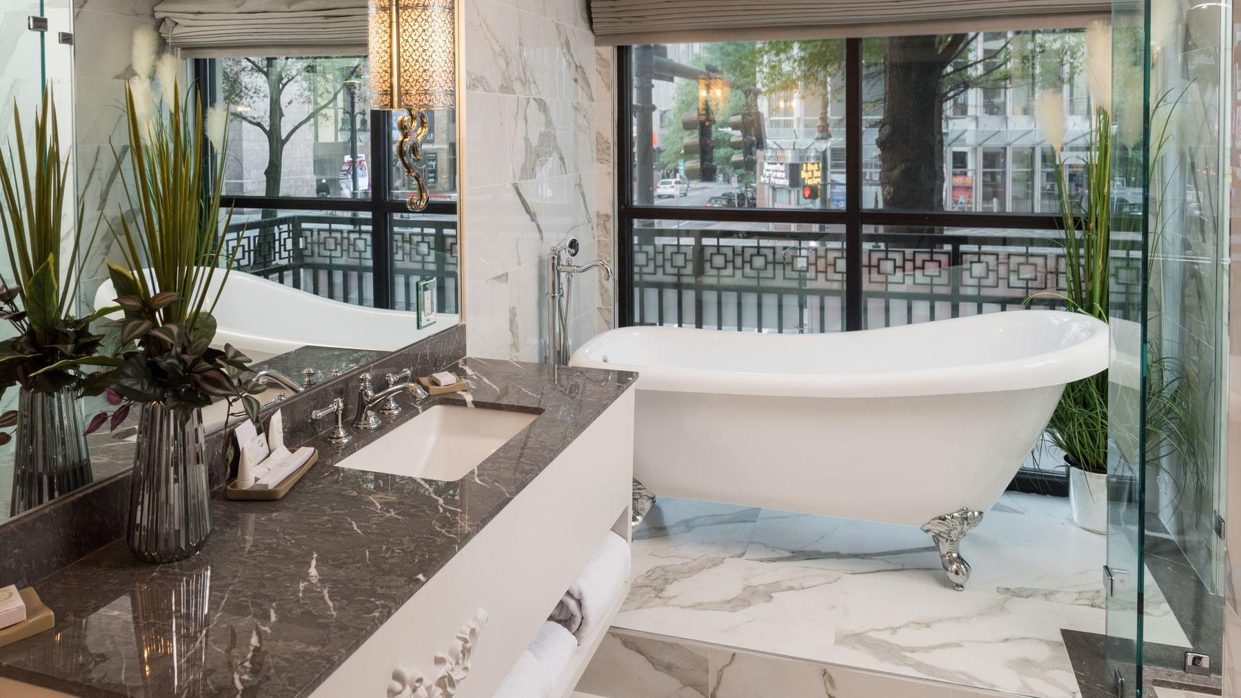 bathtub on marble floor and window
