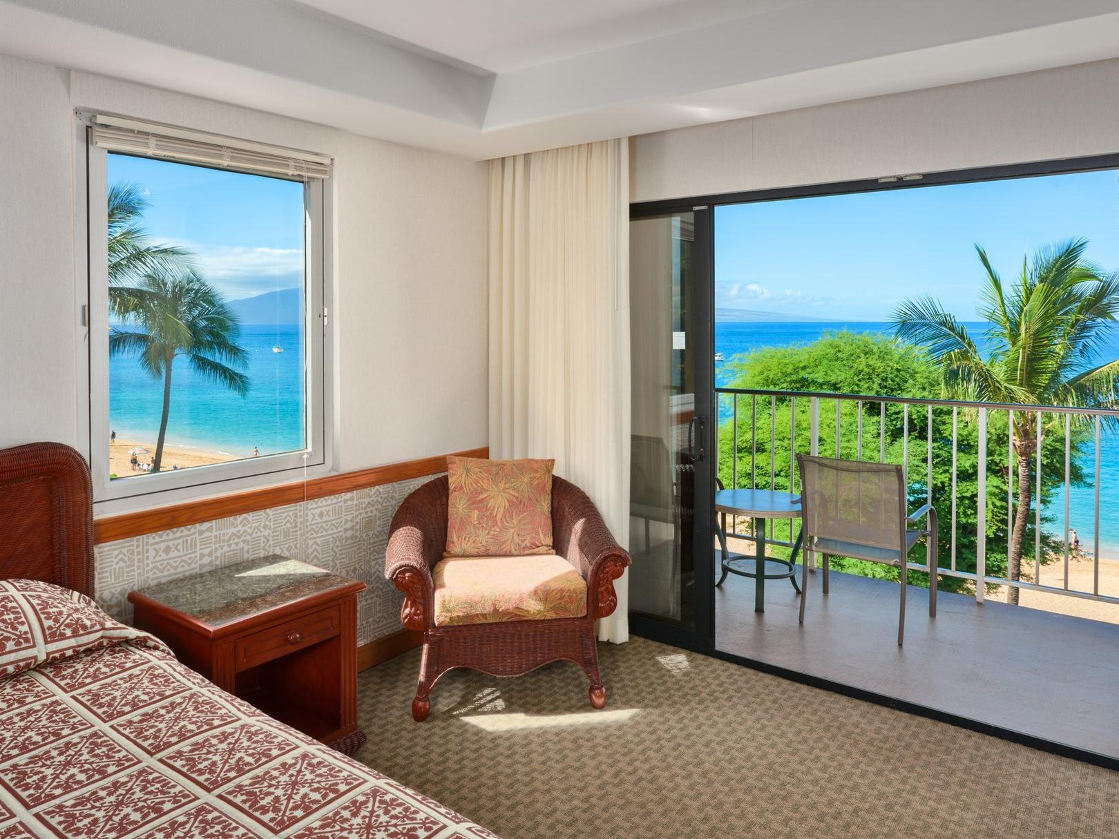 bed in hotel room with balcony overlooking beach and palm trees