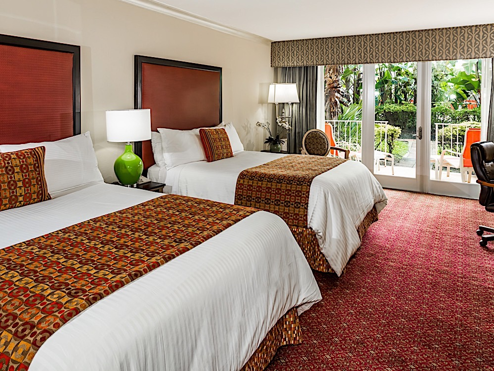 Elegant hotel room with two Queen beds and pool view.