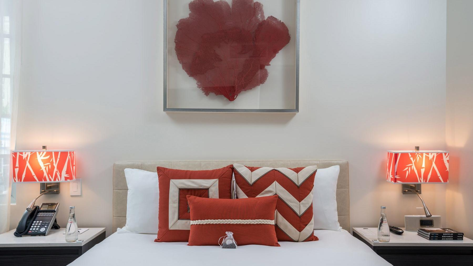 bed with white sheets and red pillows