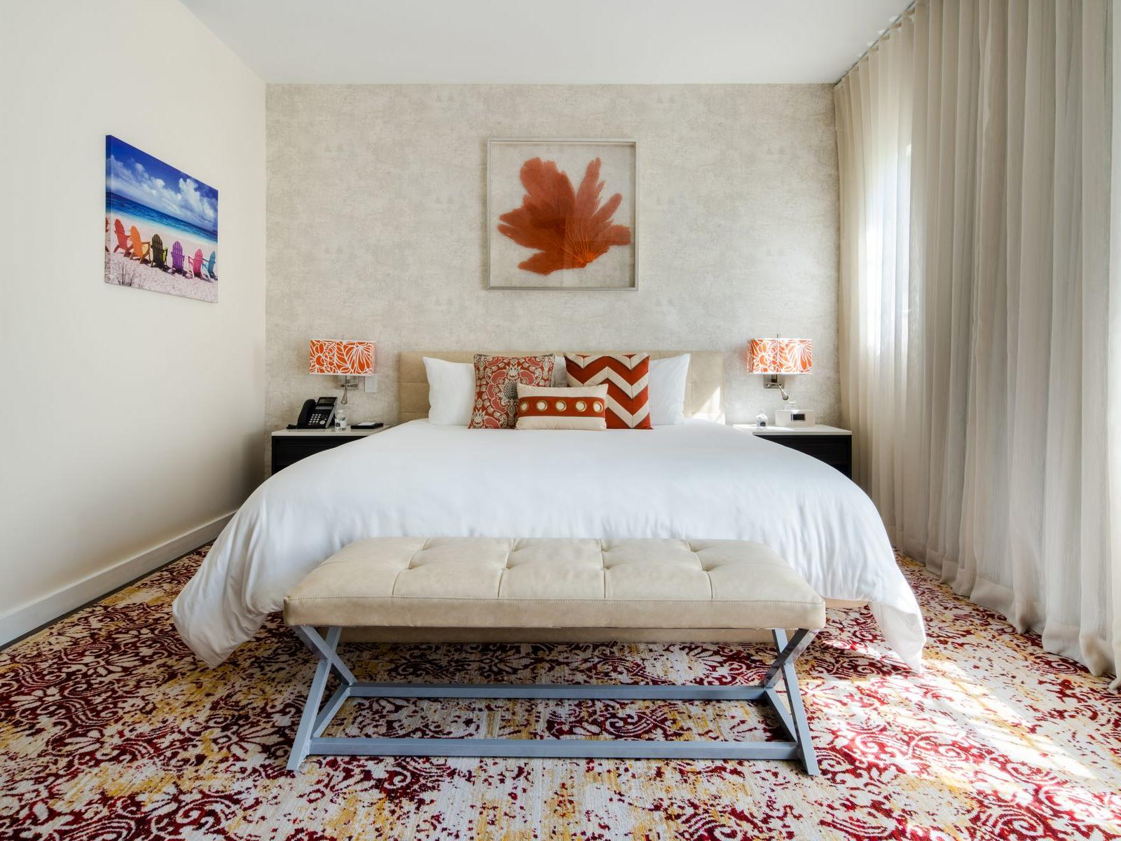 large bed in carpeted room with wall art