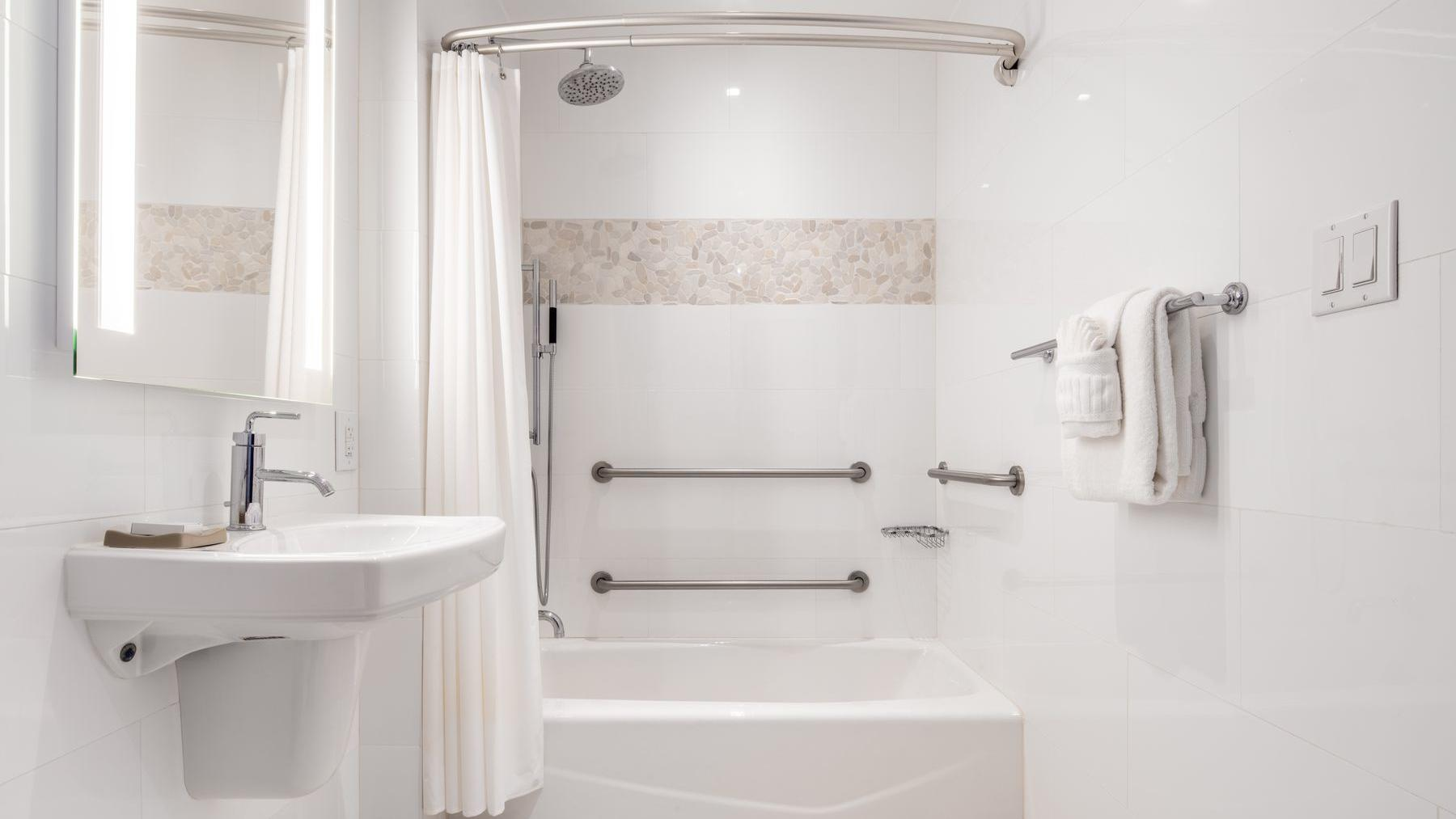 accessible bathroom with sink and shower tub