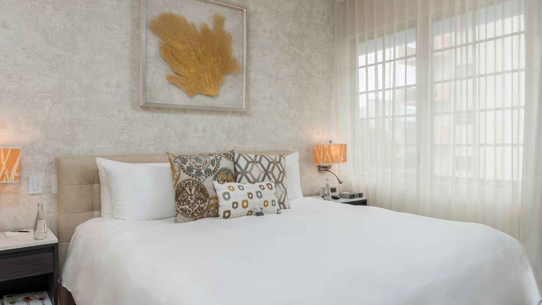 bed with white sheets and wall art