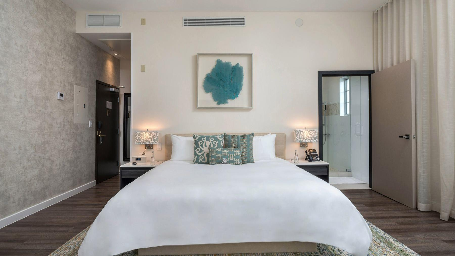 bed with white sheets and painting above