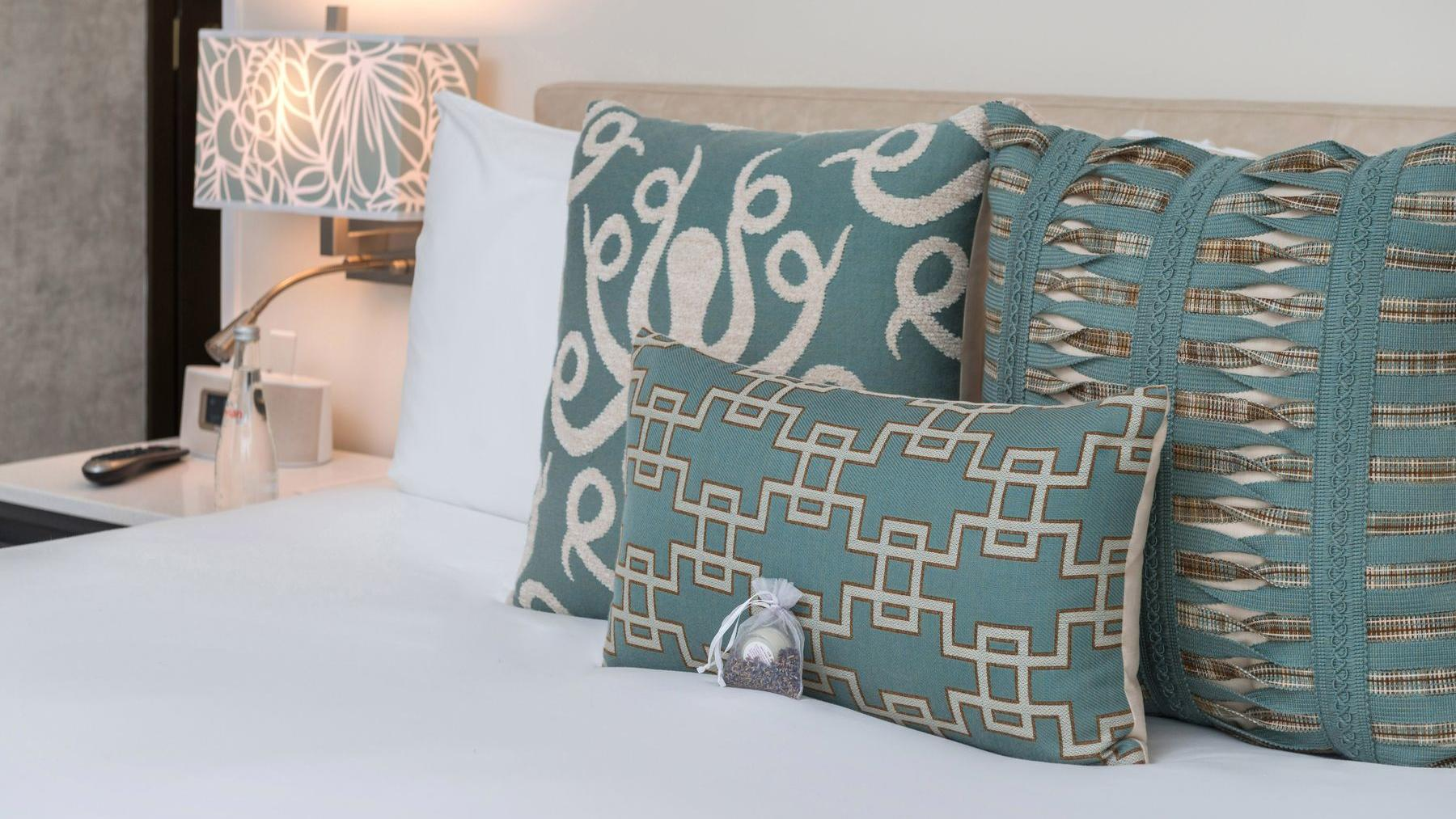 bed with white sheets and blue pillows