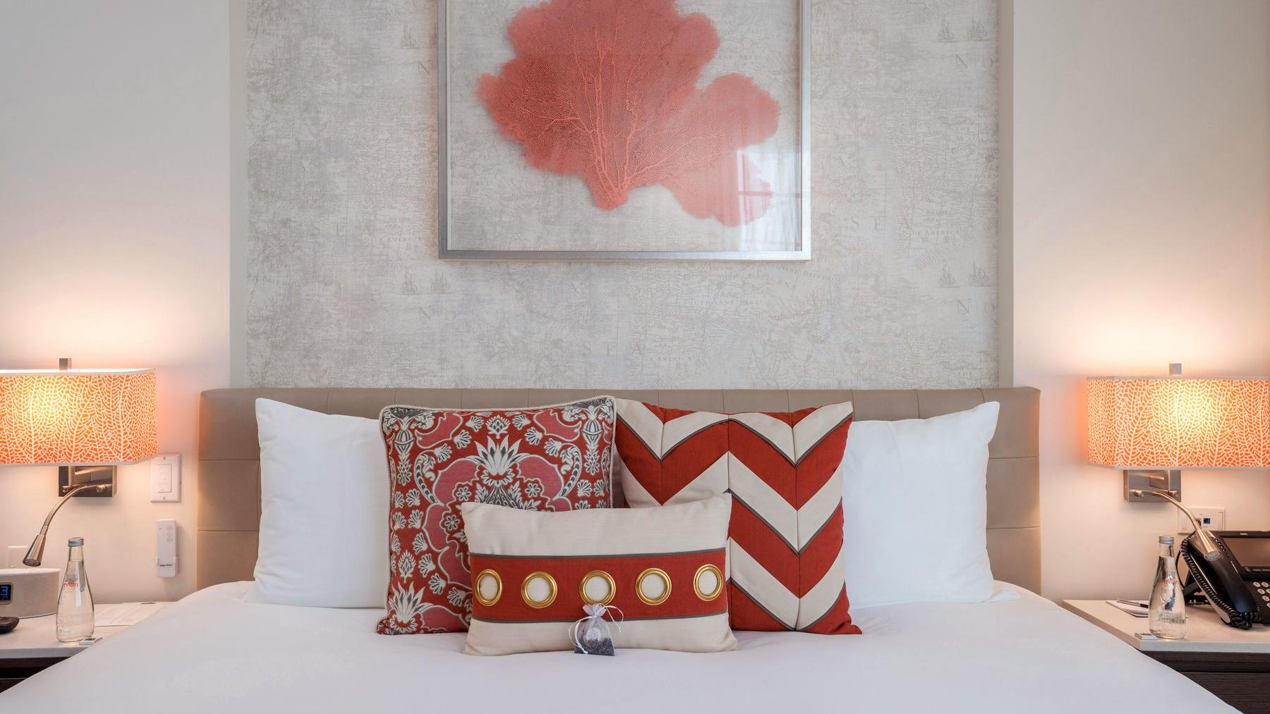 bed with white sheets and red pillow