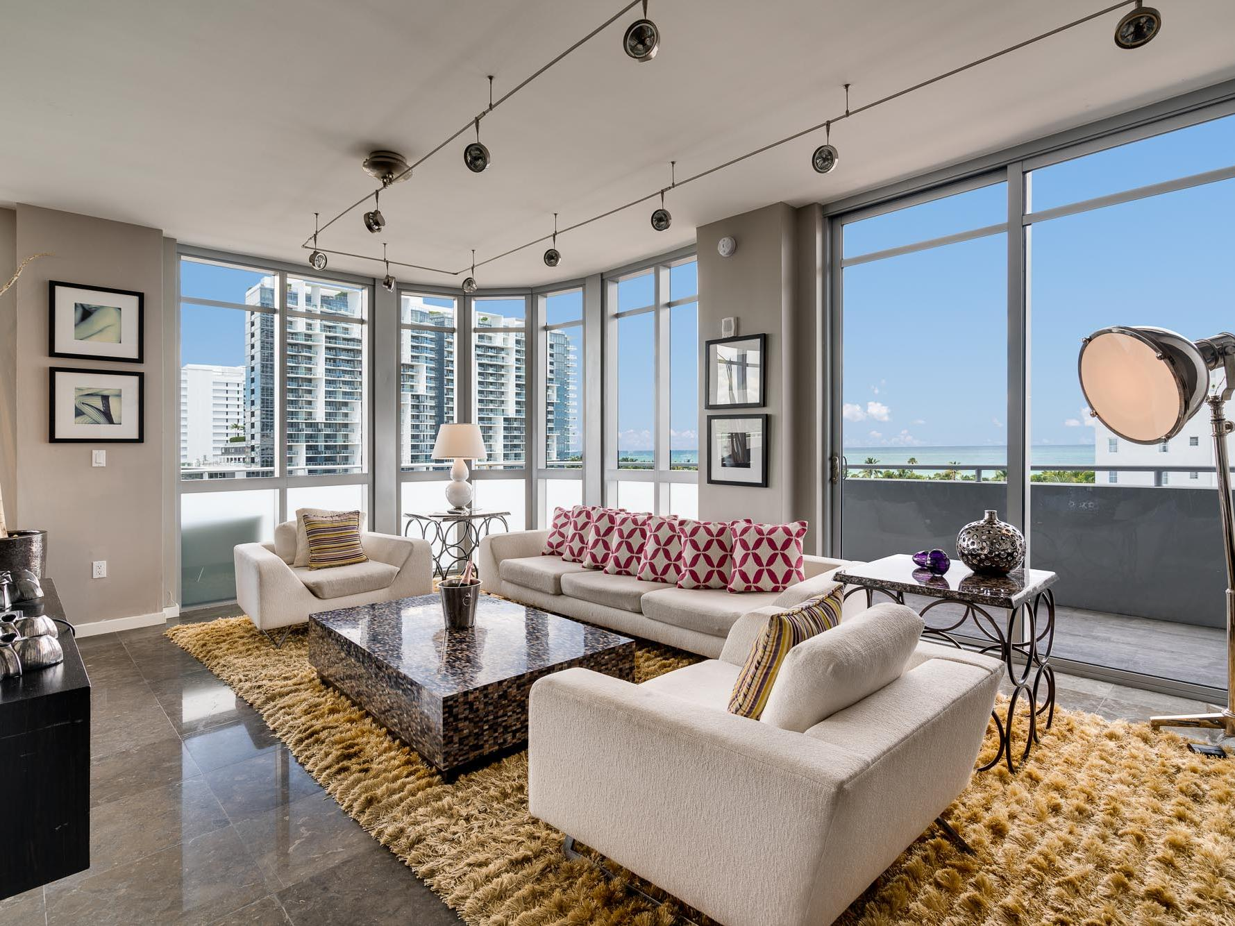 living room with sofas, large coffee table and floor to ceiling windows overlooking city