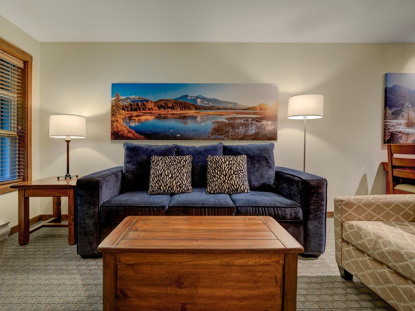 living room with blue couch and wooden table