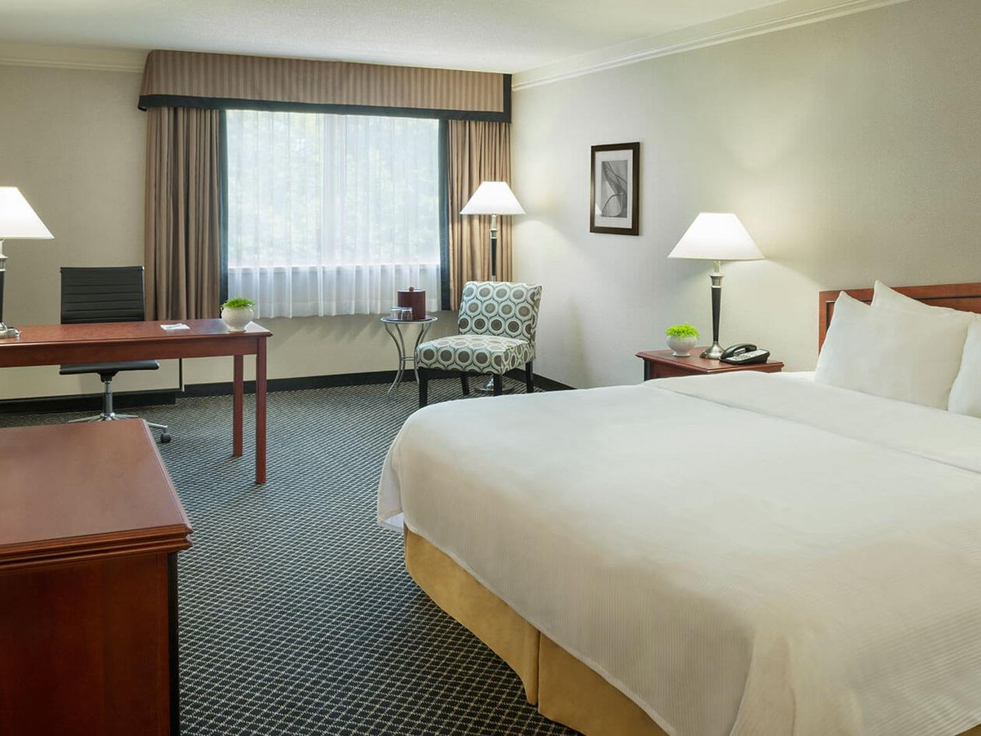 Bed in hotel room with desk and chair