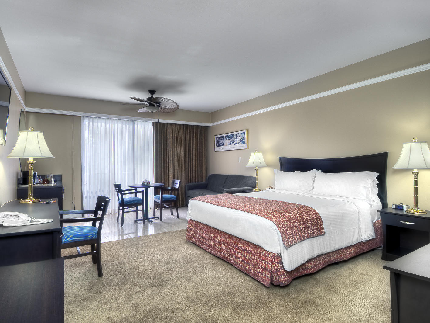 bed in carpeted hotel room with furniture