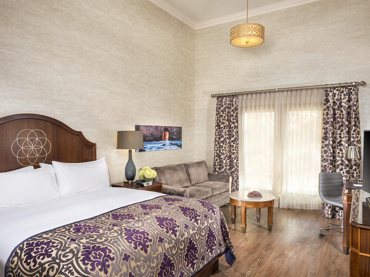 A room which includes a king size bed, sofa and coffee table, a writing desk and a flat screen TV.