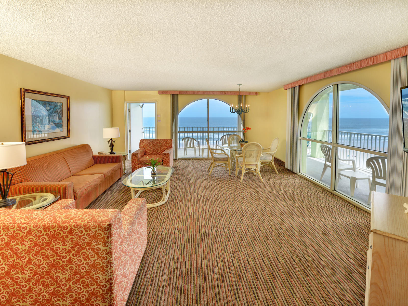 Oceanview hotel room with broad living space.