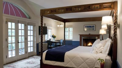 woodburning fireplace king room featuring 4-posted wooden bed, real wood fireplace, settee, table for 2, and french doors leading to private balcony