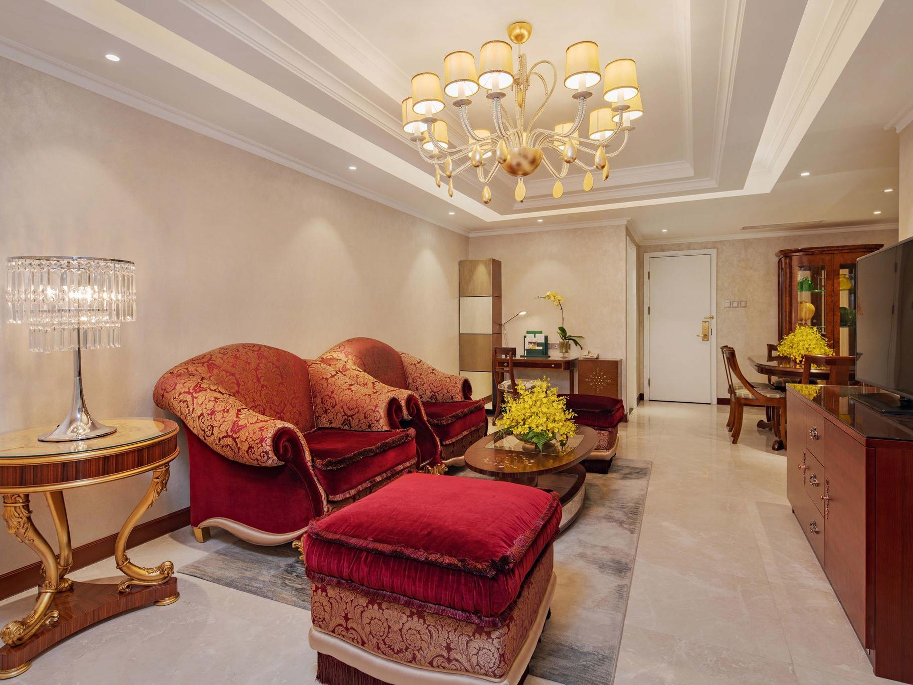 luxurious living room with maroon sofa, coffee table and television
