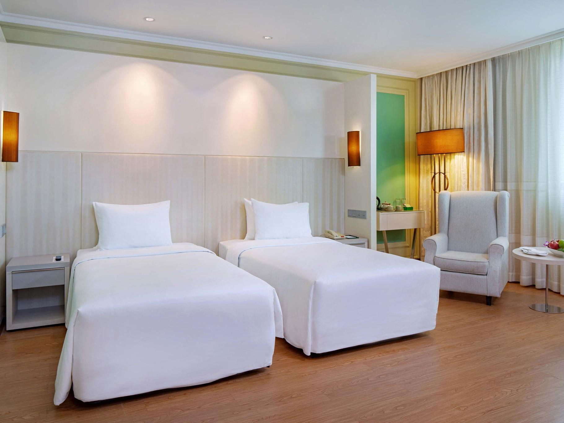 hotel room with twin bed and lounge chair