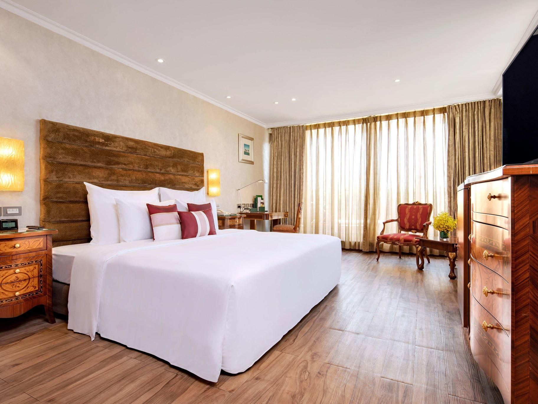 brightly lit spacious hotel room with king bed