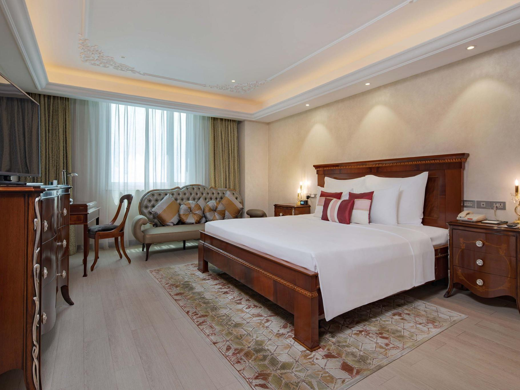well lit hotel room with king bed and wood furniture