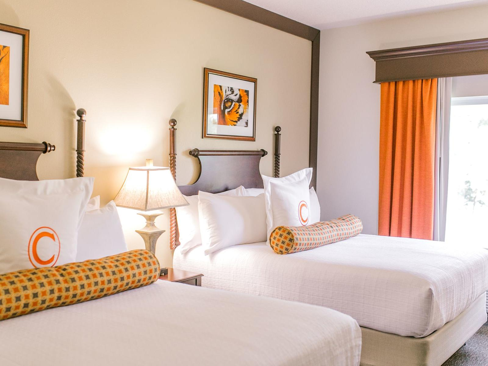 two white beds in hotel room with window and orange curtains
