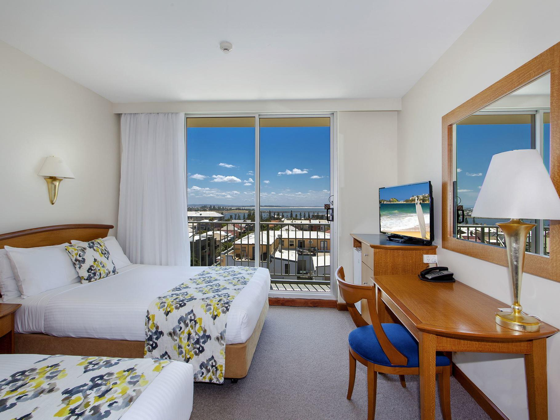 Hotel room with balcony, TV and vanity area