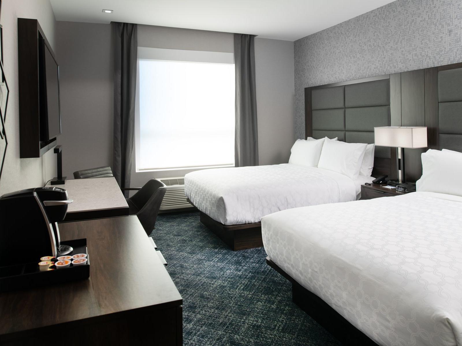 two queen beds facing tv in modern hotel room