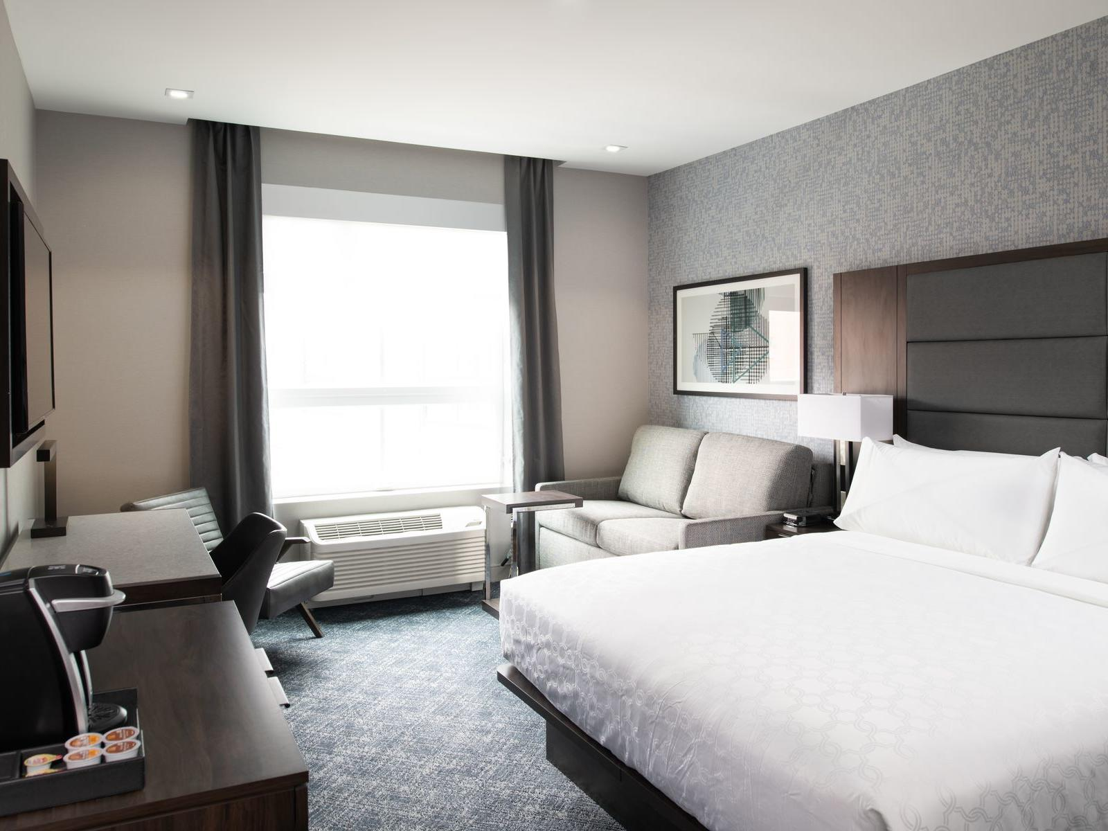 king bed and couch in modern hotel room with window