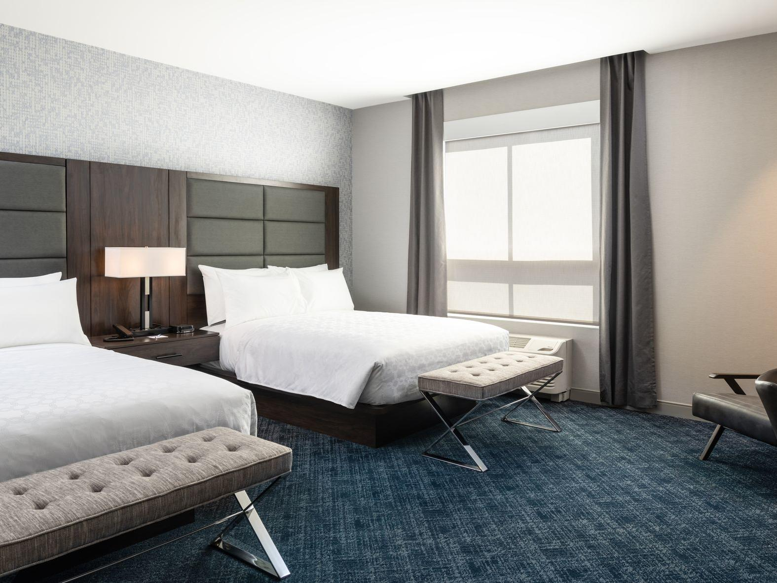 two beds in carpeted hotel room with window