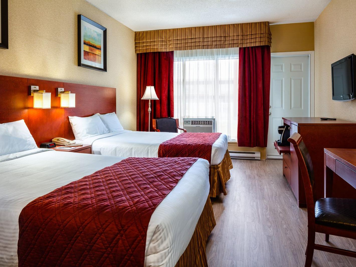 two beds in spacious hotel room with window