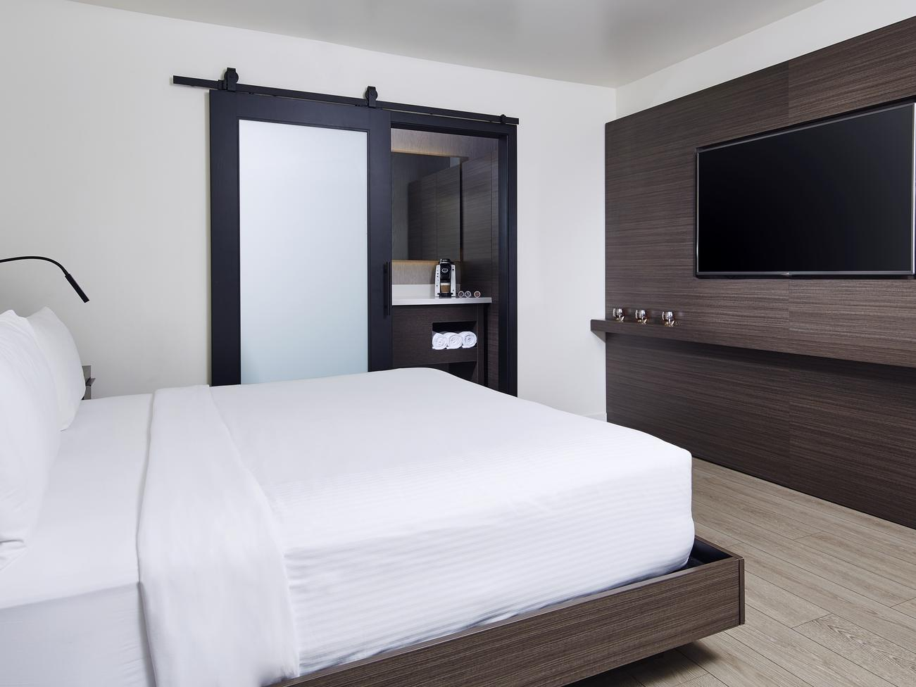 flat screen tv mounted in front of a bed