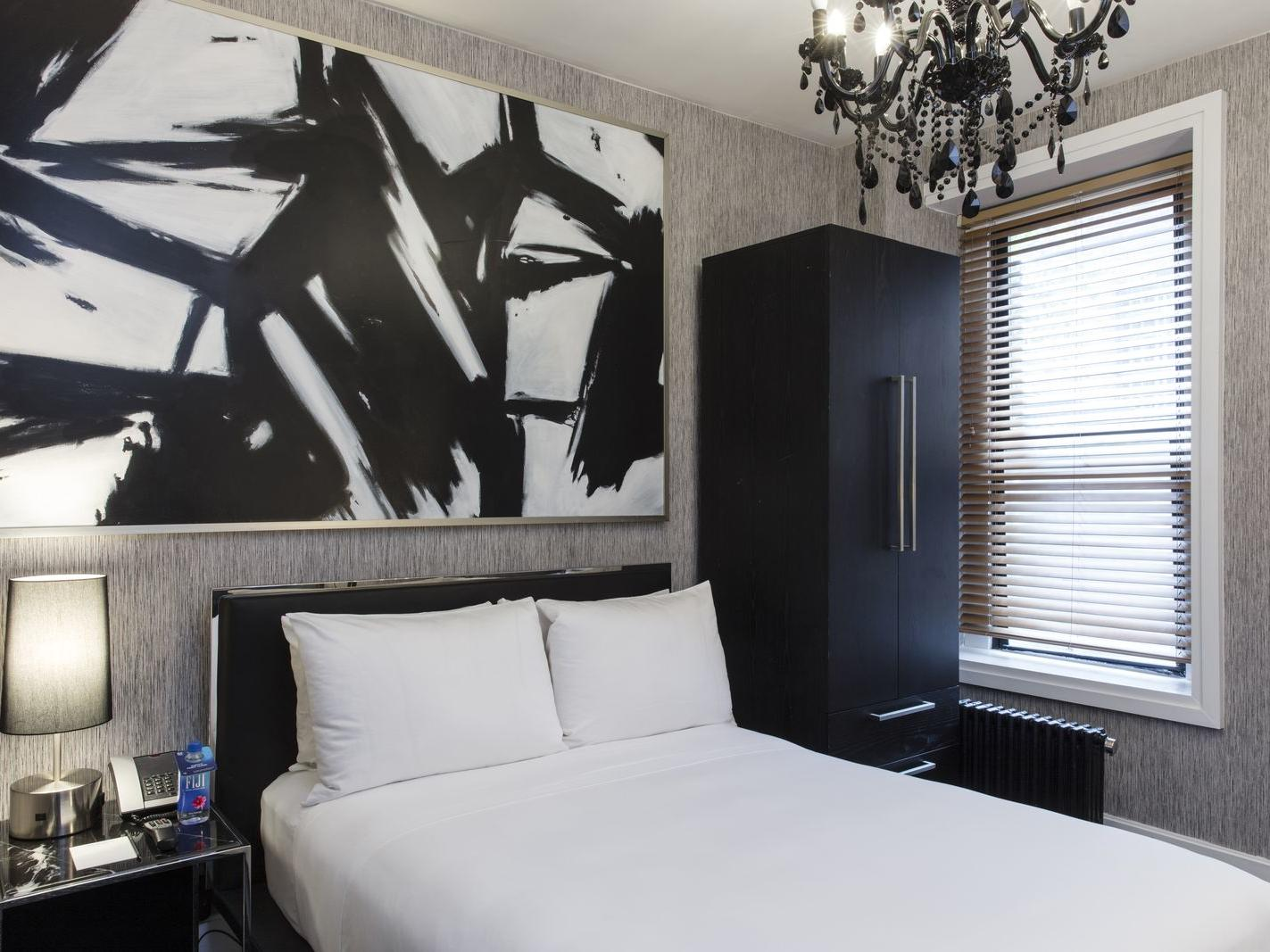 a large painting hangs above a bed