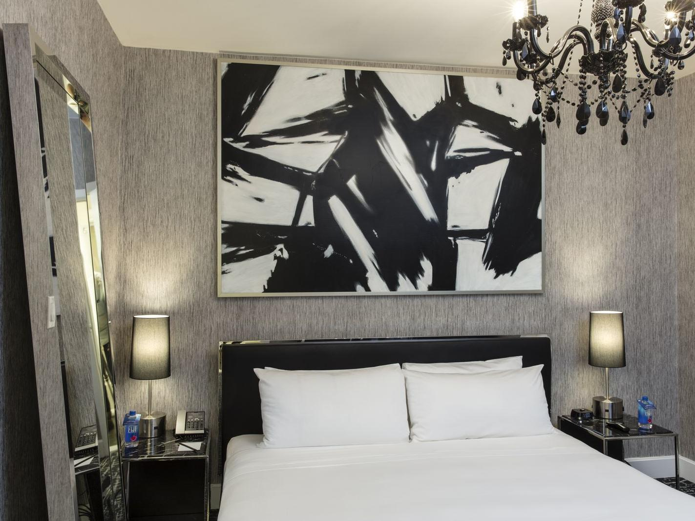 a bed in a hotel room with a chandelier