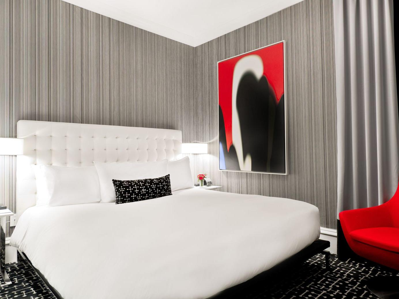 large bed next to a black and red painting