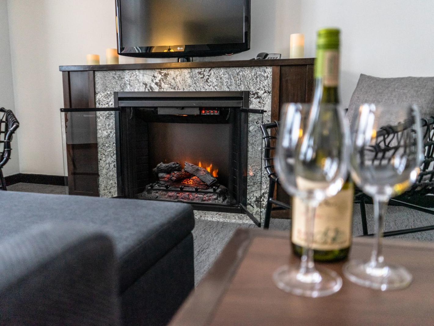 Wine bottle and glasses on table next to couch facing tv and fireplace