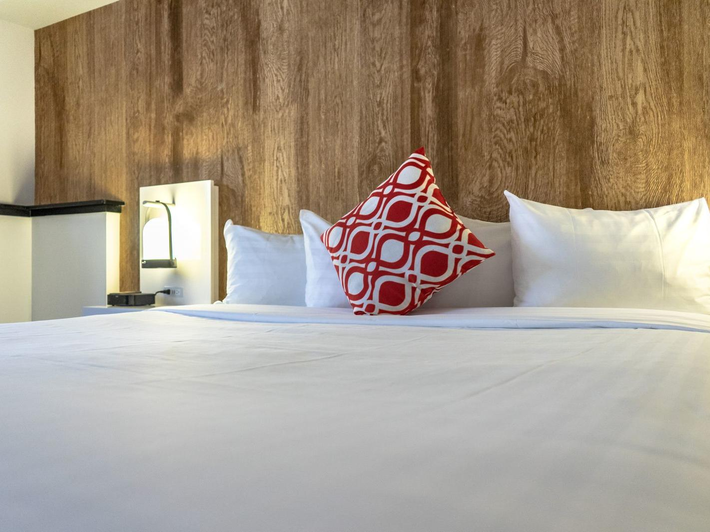 Bed in hotel room with wooden walls