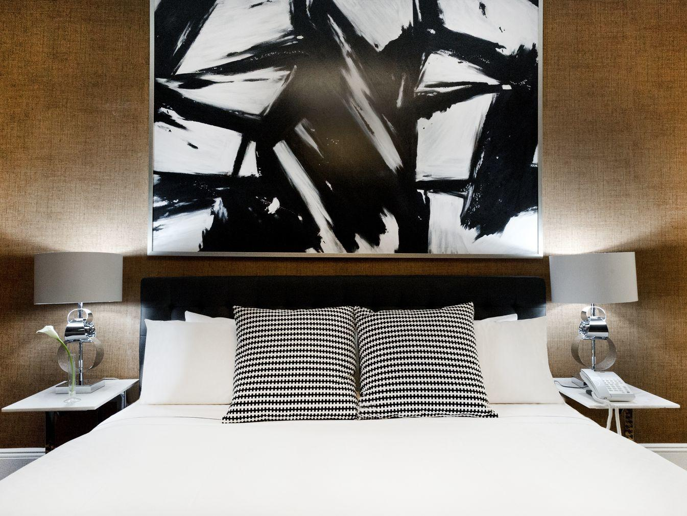 a painting hanging above a bed