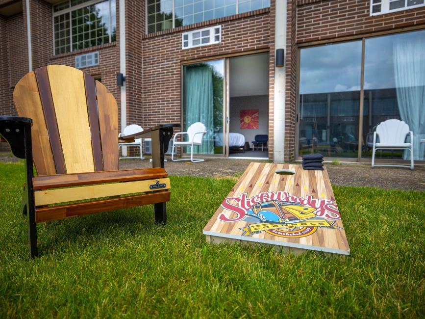 a wooden chair and cornhole board