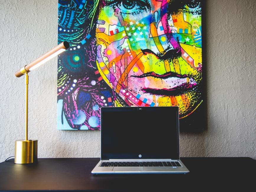 a laptop on a desk in front of a Jim Morrison painting