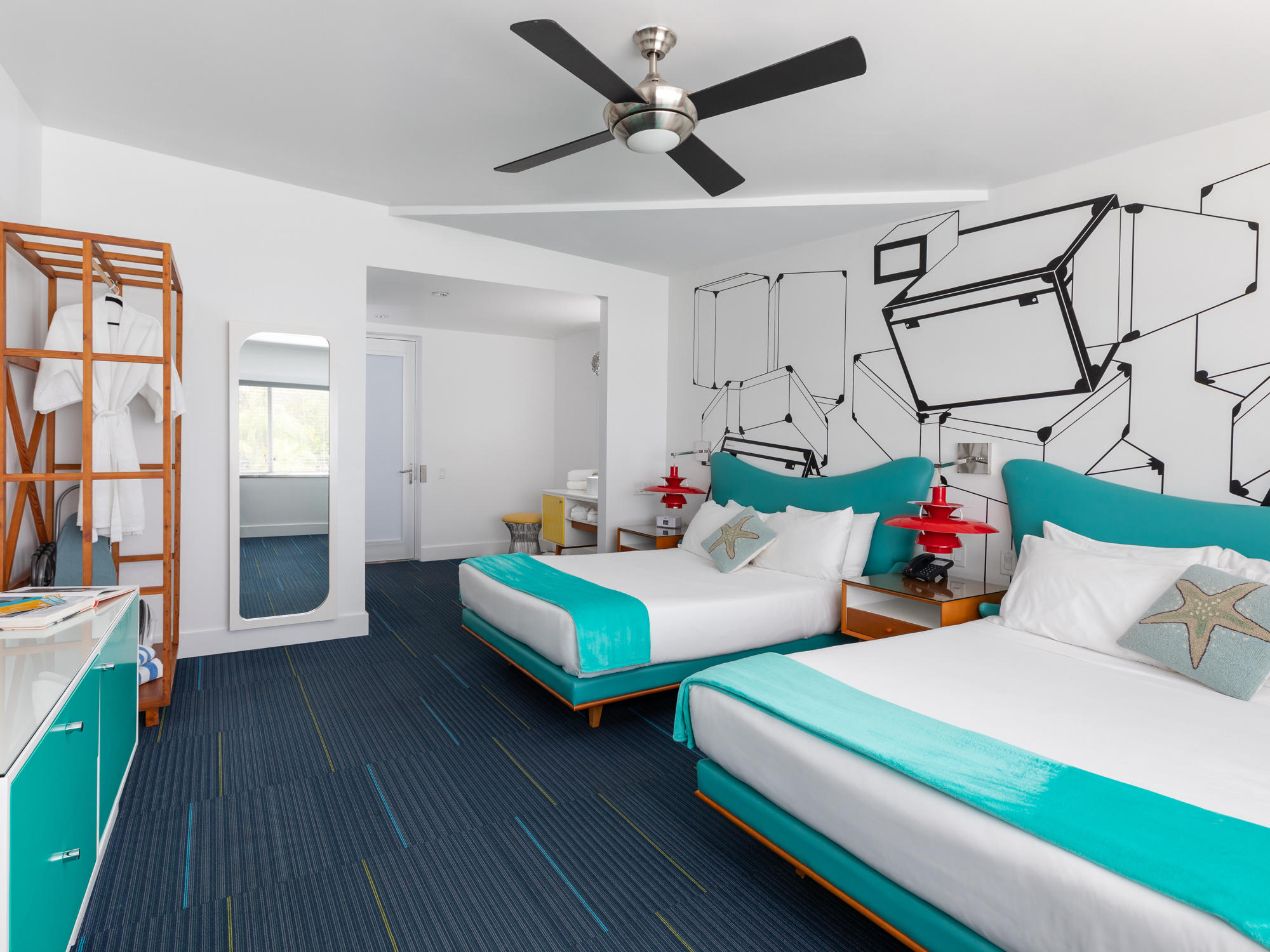 Image of the entire Skylark Doubles room that includes two full size beds, the hand stenciled wall, the bathroom vanity and the wardrobe with robes and an ironing board