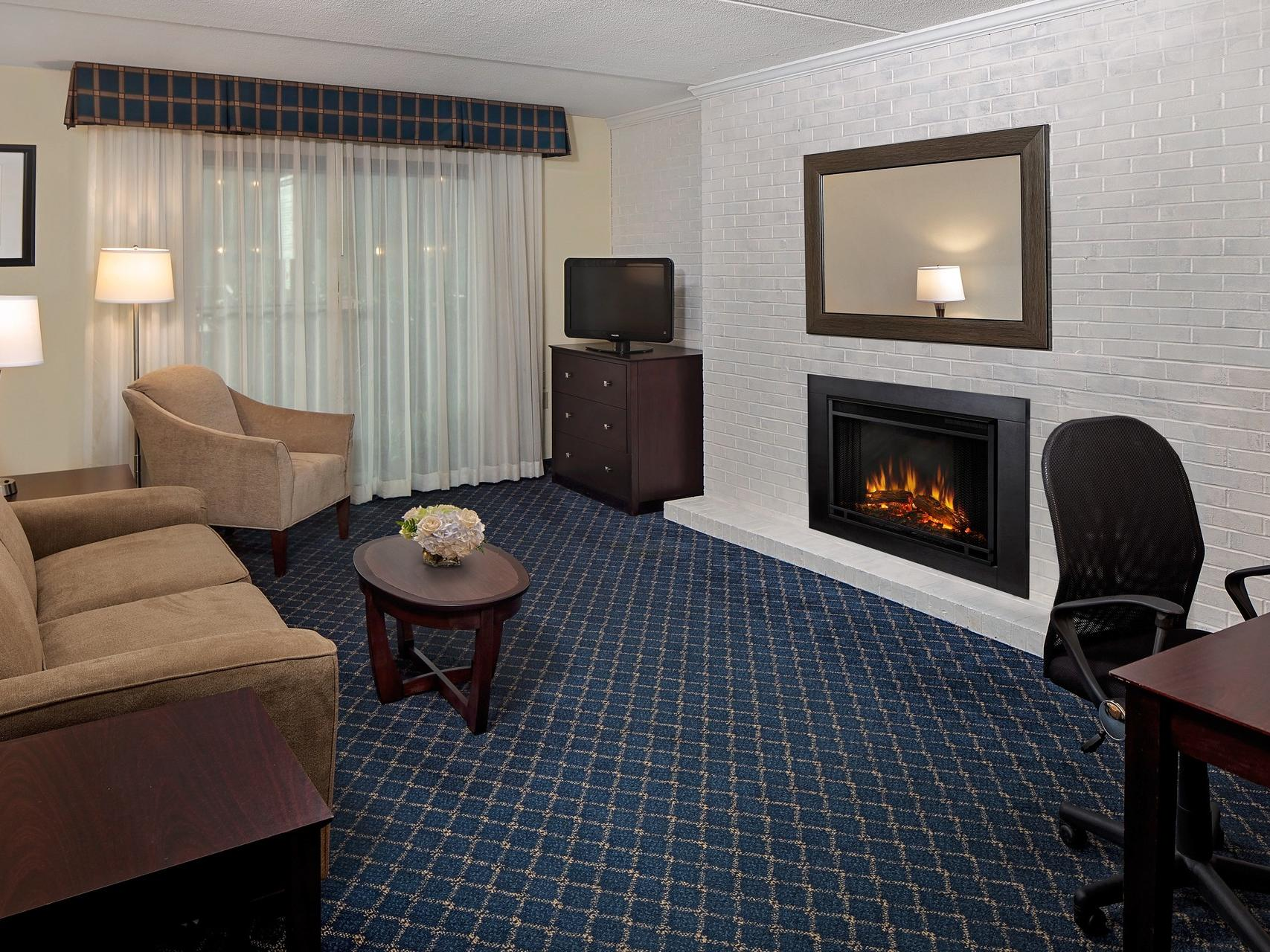 Brown couch in hotel room with fireplace