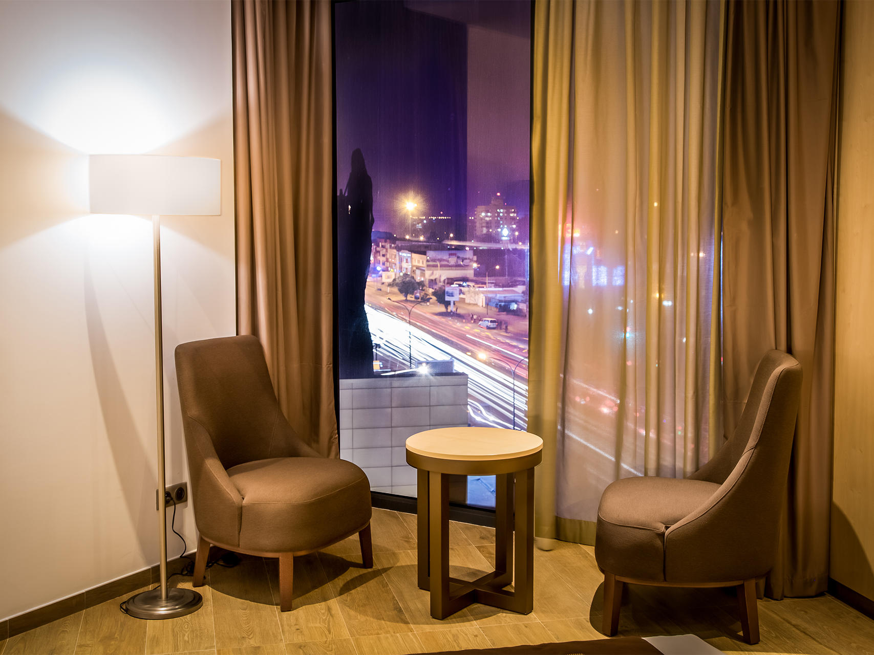 Two chairs and one coffee table with a window with the city view behind of Standard room in the Azalai Hotel Abidjan