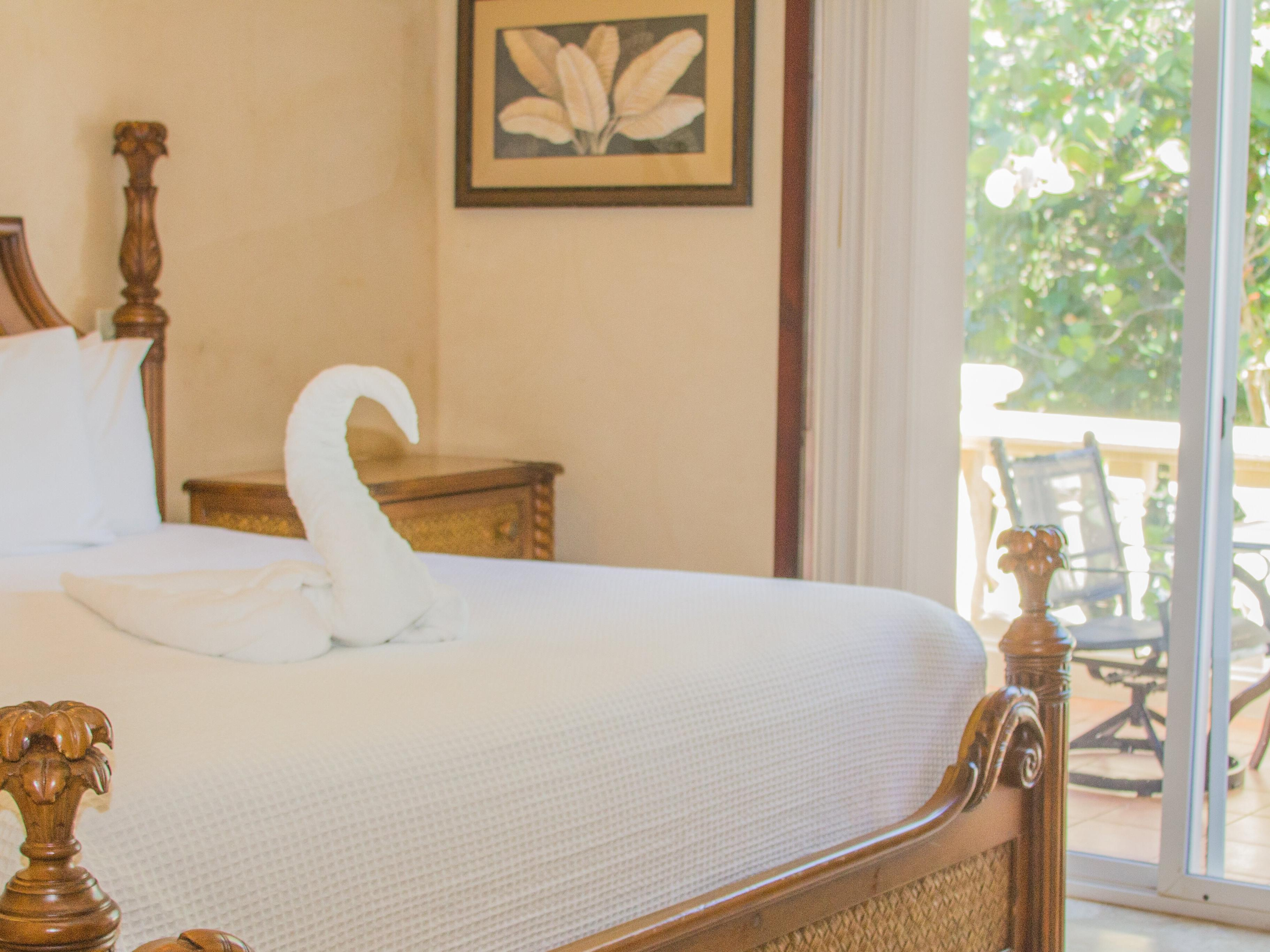 room with bed and towel folden into swan