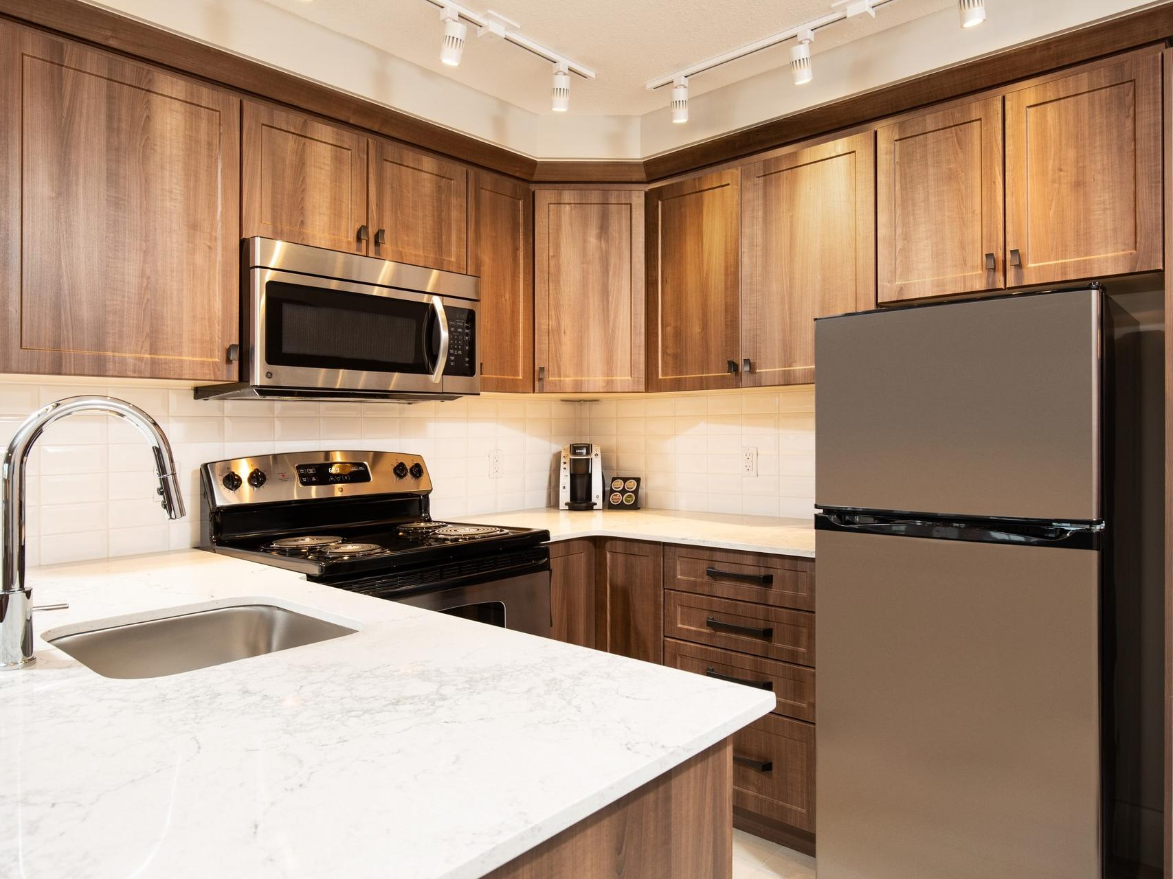 a refrigerator, microwave, and stove in a kitchen