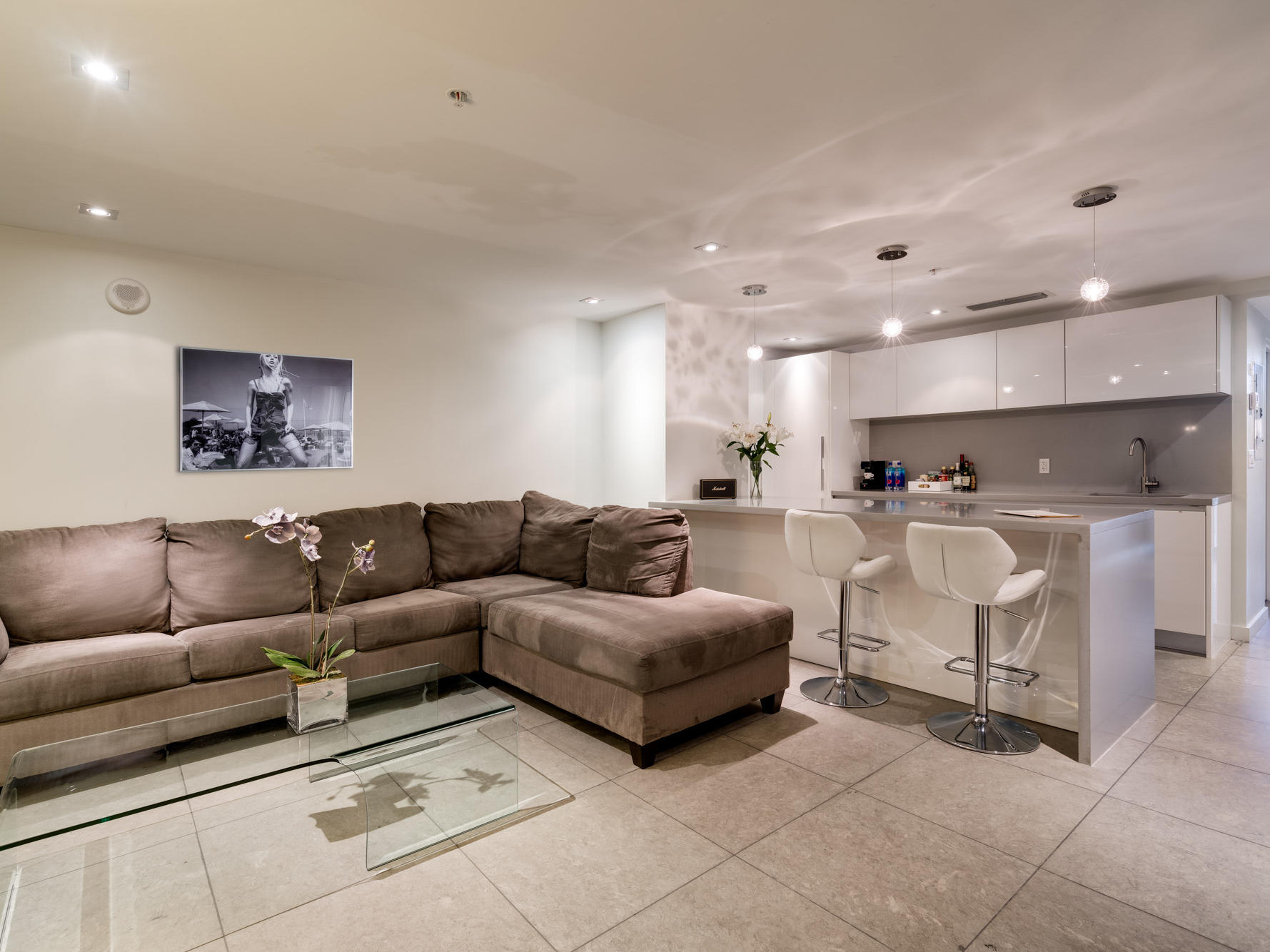 living room with grey sectional, glass coffee table and white kitchen