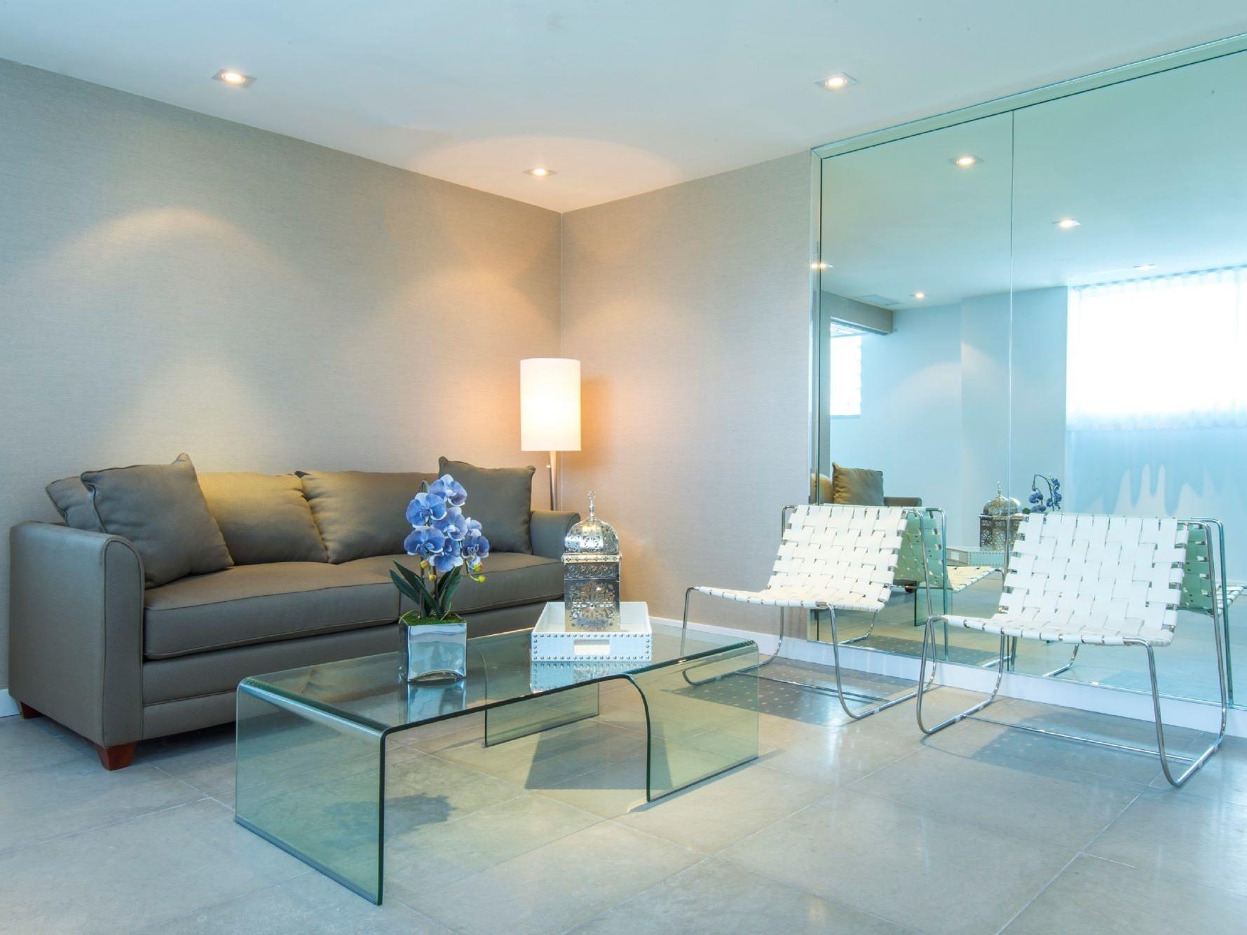living room with grey sofa bed, glass coffee table and white side chairs
