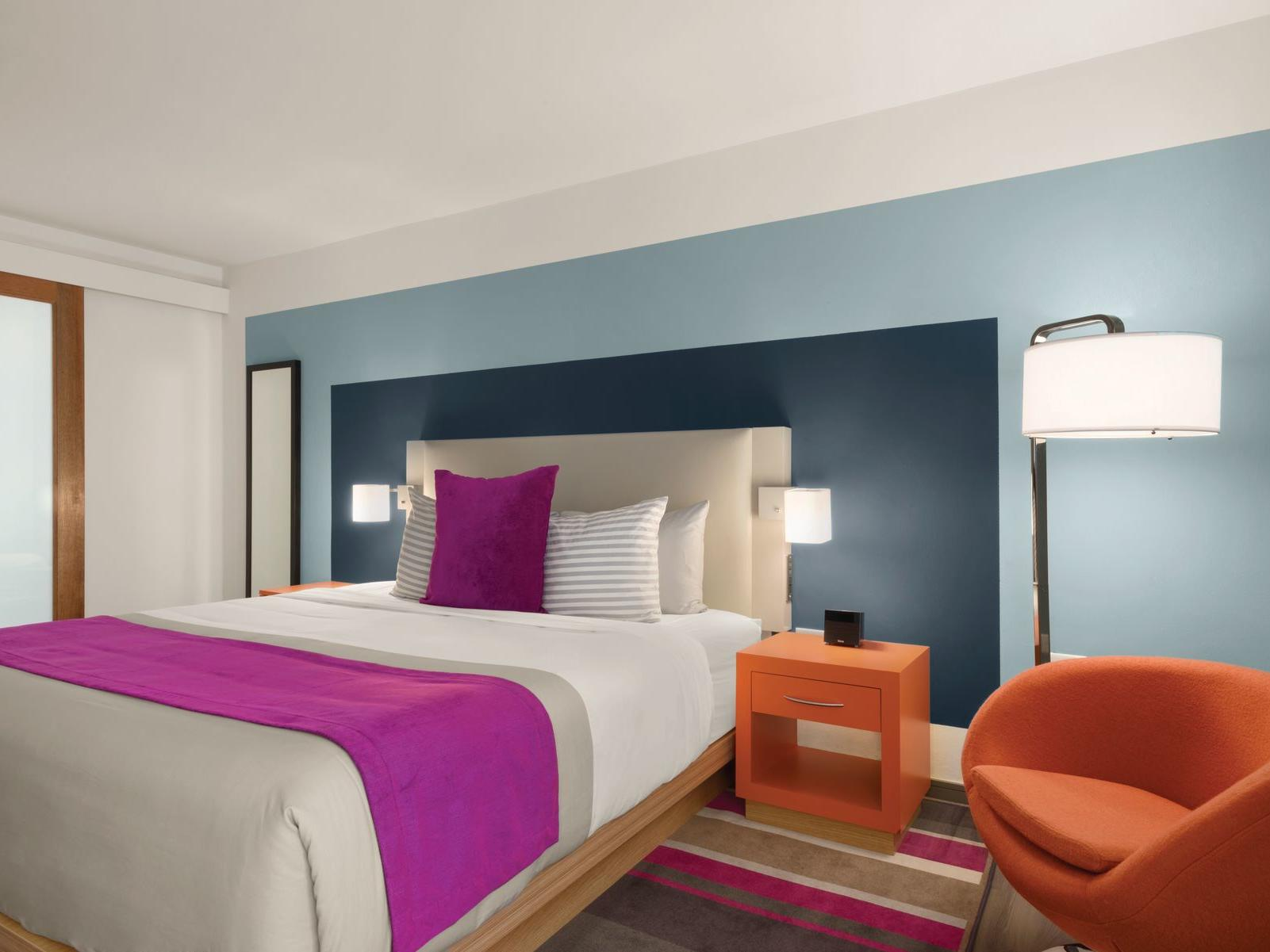 TRYP by Wyndham Isla Verde room with king bed, accent chair and lamp