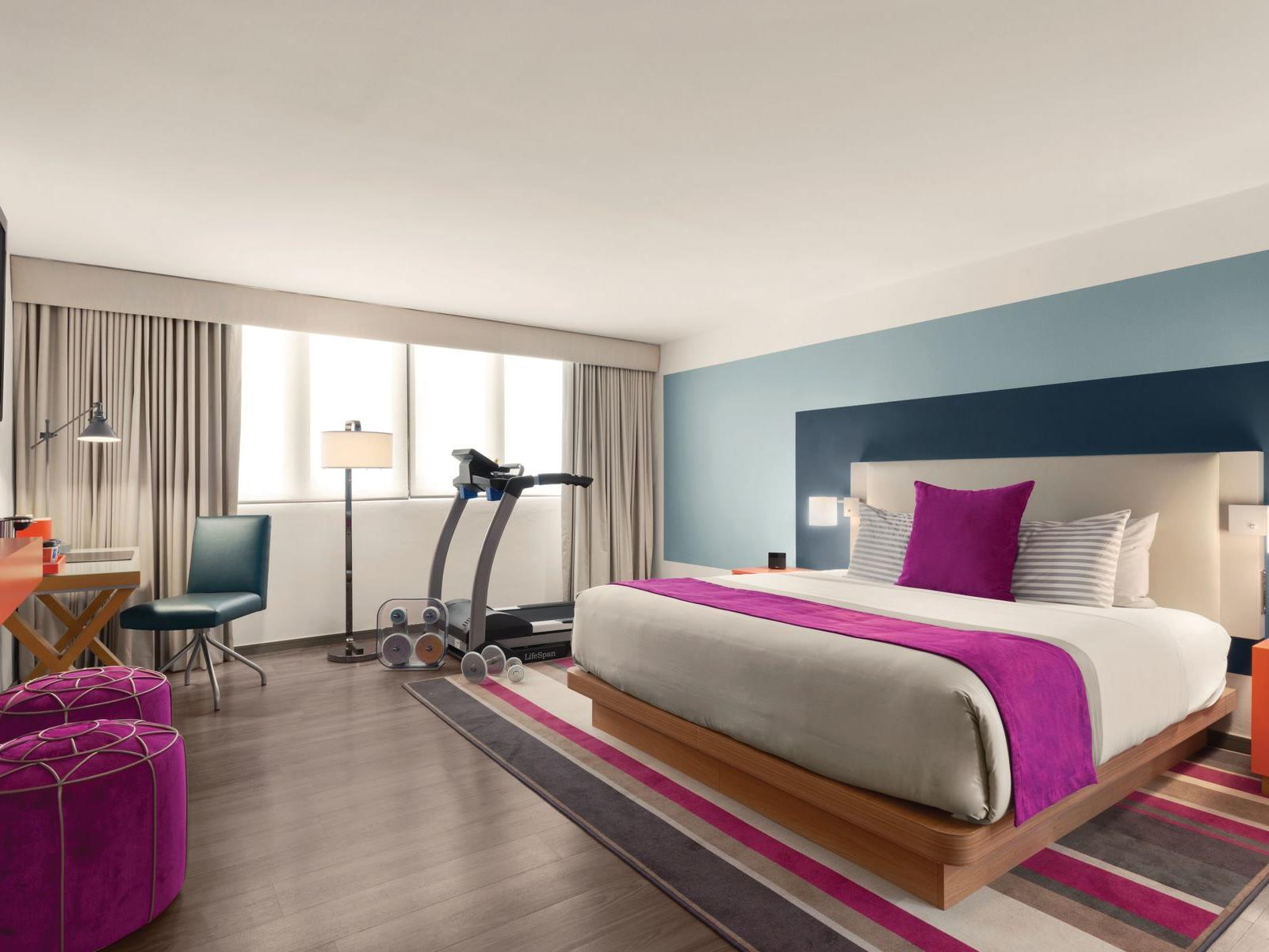 TRYP by Wyndham Isla Verde hotel room with king bed, treadmill and dumbbells near desk