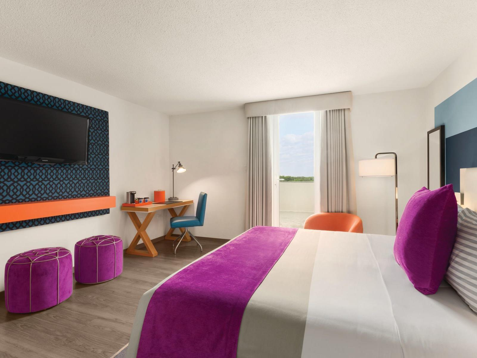Isla Verde room with king bed, television on wall and window