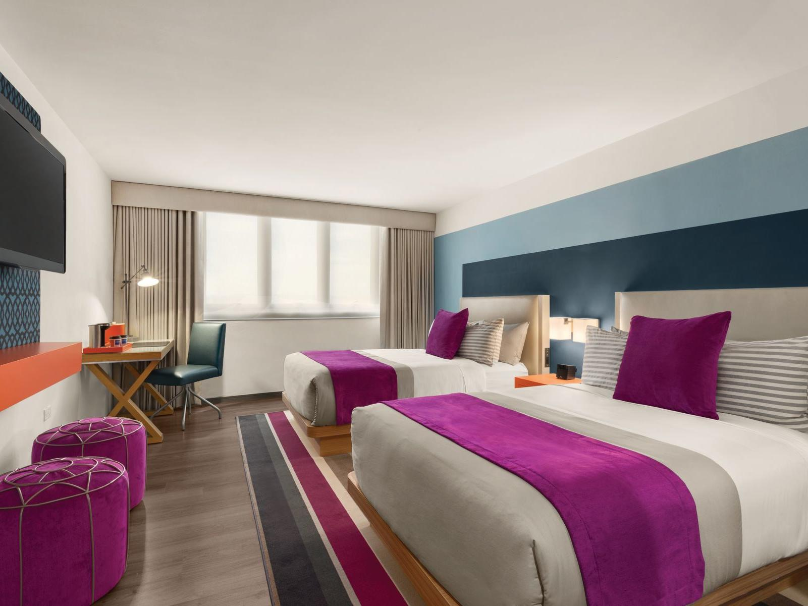 TRYP by Wyndham Isla Verde hotel room with two double beds, desk and television on wall