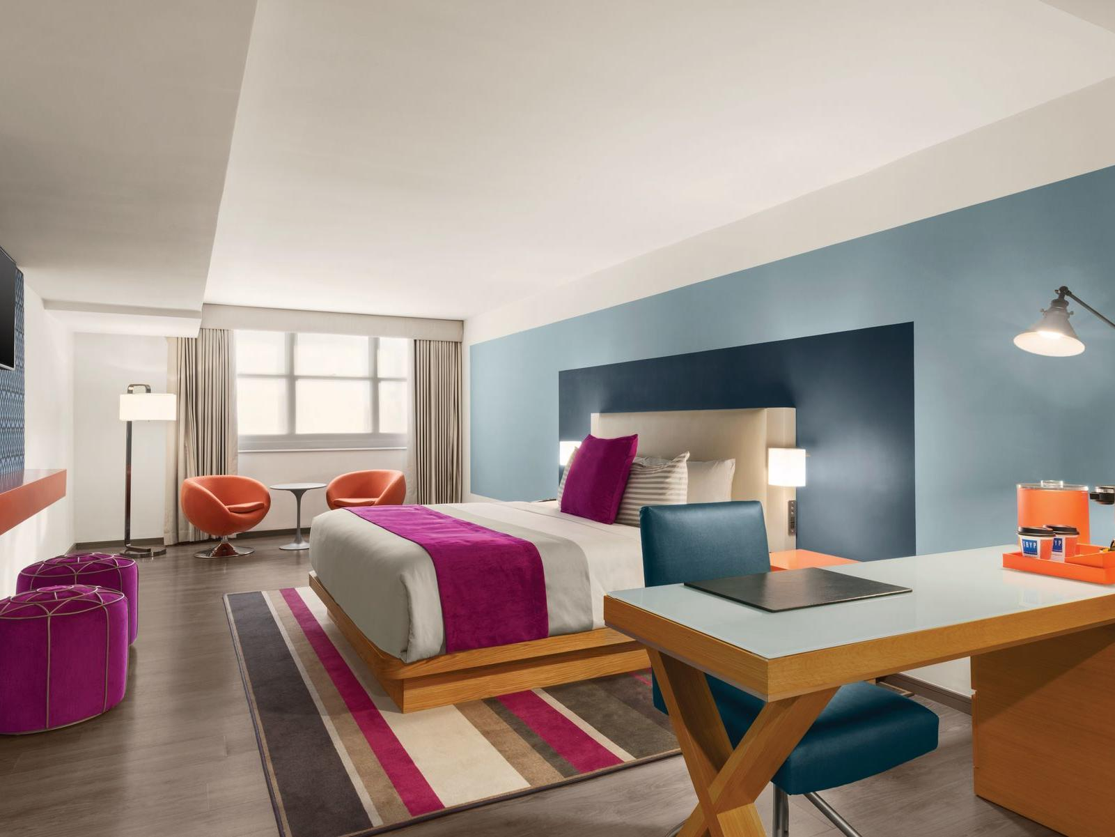 TRYP by Wyndham Isla Verde TRYP by Wyndham Isla Verde hotel room with bed, desk and accent chairs with table