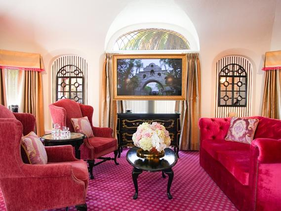 living room with pink sofa, chairs and carpet
